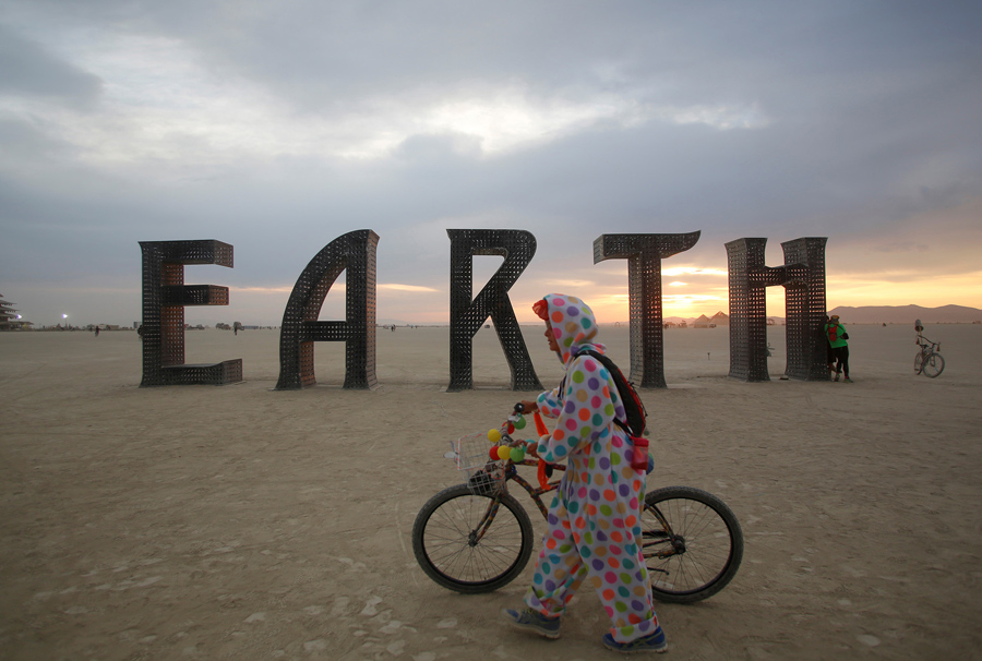 A participant walks past an art installation as approximately 70,000 people from all over the world gather for the 30th annual Burning Man arts and music festival in the Black Rock Desert of Nevada, U.S. August 30, 2016. REUTERS/Jim Urquhart FOR USE WITH BURNING MAN RELATED REPORTING ONLY. FOR EDITORIAL USE ONLY. NOT FOR SALE FOR MARKETING OR ADVERTISING CAMPAIGNS. NO THIRD PARTY SALES. NOT FOR USE BY REUTERS THIRD PARTY DISTRIBUTORS - RTX2NN7P