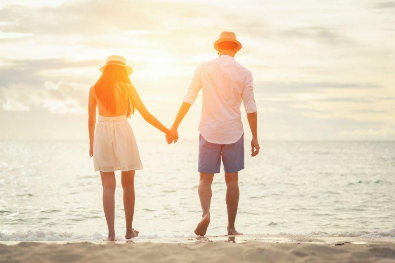 カップルが海沿いで手を繋ぐ