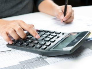 Close-up of calculator with hands taking notes