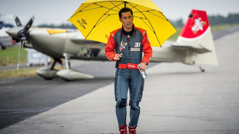 Yoshihide Muroya of Japan walks on the airport during the training for the fourth stage of the Red Bull Air Race World Championship in Gdynia, Poland on July 26, 2014.