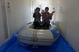 こちらは環境地球化学研究室のブースです。この研究室では、水や森林、大気など地球規模で環境の変動・変化を研究しています。今回は先生や学生が調査の際に実際に使用しているボートを展示。参加者の方に乗っていただきました。手に持っているのは深いところの水を採取する機械。溺れないようにライフジャケットも着用していただきました!