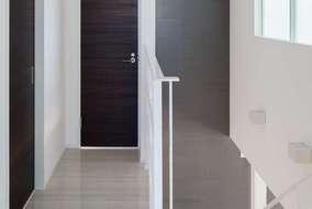 2階吹き抜け廊下の壁はリビングに張ったタイルをつなげて張っています。空間のつながりを演出しています