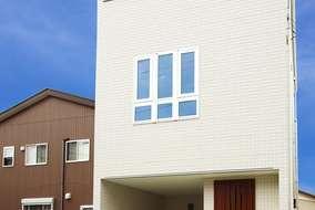 外観は白一色でまとめたタイル調。防犯に配慮して1階の窓は小さく少なくしました。