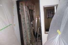 現事務所に養生をしてドアを付け、断熱材を入れ石膏ボードを貼りました。