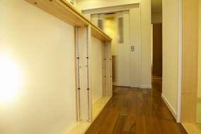 エレベーターへと続く廊下の手すりにはガラスを採用し、光を採り入れられるように工夫。