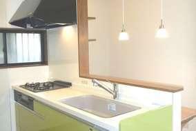 扉もお気に入りのグリーンを選定。対面部分の照明もペンダントとスポットにして、モダンなキッチンに。