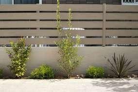 隣家との境界は塗り壁と人工木のフェンスで。