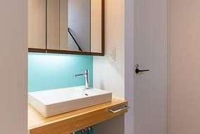 廊下に付けた多目的に使う製作品の洗面化粧台です。アクセントにティファニー色のクロスを張っています。