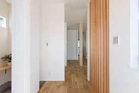 玄関とリビングとの間仕切りは木製ルーバーを使い広さを感じさせています。シューズクロークもあります