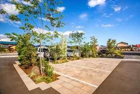 緑に囲まれた昼間の来客用駐車スペースです。