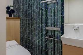 階段下を利用したトイレになります。背面には造作収納を作っています。壁にはガラスモザイクを張っています