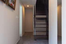 玄関に入ると石目調の床とストリップ階段が目を引く玄関です。