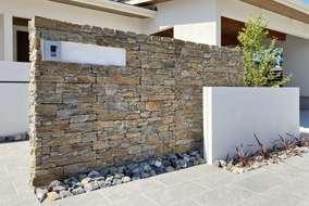 門壁は重厚感のある石貼りでしあげました。 右側には低めの真っ白な壁を組み合わせました。