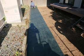 防草シート(ザバーン)を敷き、人工芝を敷設しました
