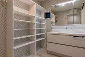 洗面所は大きな洗面化粧台、収納たっぷりな造作棚もつけさせていただいています