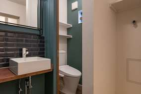 洗面化粧台にはアクセントにタイルを張りトイレの中にはアクセントのクロスを張っています。