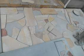 石貼り工事の様子。同じ形の無い自然石は職人のセンスも必要です。