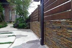 既存コンクリート擁壁は石貼りにしました。石貼りの中に表札が埋め込んであります。 目隠しは板塀です