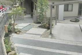 玄関と駐車スペースへのアプローチ部分に板石を並べ、植栽後にゴロタ石を並べていきました。