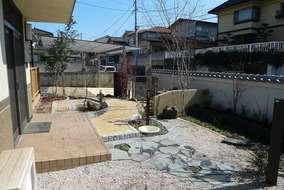 玄関までのアプローチに、石を張り、塀側には樹木を植える花壇を作りました。