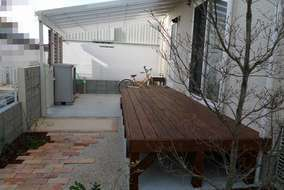 家の裏手にウッドデッキを設置し、勝手口前のテラスの下に洗濯物を干すスペースを作りました
