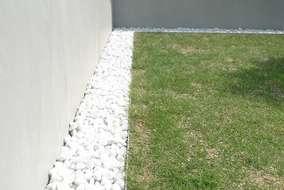 芝生の周りに白い砂利を敷き塀との境界を際立たせました