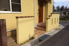 ジョリパットの塗り壁にレンガの笠木が乗っています。