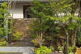 玄関をさりげなく隠す目隠し塀は、自然石で仕上げ、植栽、景石など自然な和空間をとしました