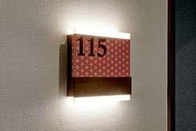 居室サインです。 ブラケットライトに造作サインを取り付けました。 模様や色は日本古来のものを採用。