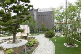 右は形状記憶の人工芝で踏み倒しても徐々に立ち上がり、植木はアオダモを植栽。根元はピンコロの円形花壇。