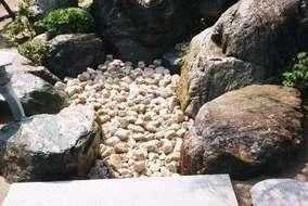 枯山水の流れに玉石を敷きました。  上段は大きい・下段は小さい玉石です。 石橋はみかげ石。