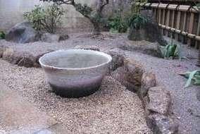 益子焼の水蓮鉢。 水蓮を植えたばかりなので水が濁ってます。草花は、つわぶき・万両・シャクナゲの移植。