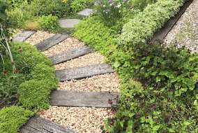 庭の中に大きく描いたS字の枕木アプローチ。間のカラーストーンは施主様が。