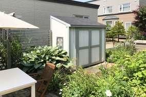 庭の雰囲気に合わせて物置もウッド系をチョイス。緑が映えるよう塗装は白に。
