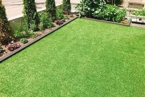 お子様が裸足で遊べる人工芝。周りには花壇と菜園を配置。仕切りの木材の色は外壁のダークブラウンに合わせ
