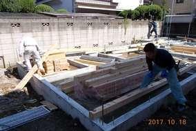 基礎の上に土台を設置するべく、プレカット木材を運び入れてます。木材には防虫のため薬剤を塗ります