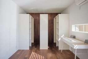 居室には大きな本棚収納を造作しています。壁には床と同材のウォールナットを使っています。