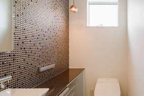 トイレの壁にはタイルを張りました。壁の隅には小さなコードペンダントがアクセントになっています。