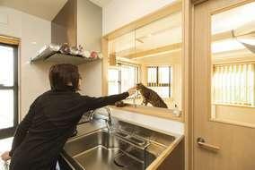 キッチンには室内の様子がうかがえるようにガラス窓に。作業にも集中できて一石二鳥だ。