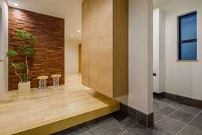 玄関は広くシューズクロークにつながる空間になります。壁には木のタイルが来客者を迎い入れます。