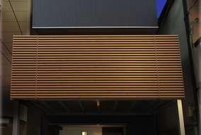 外壁はネイビー色の外壁を使いました。バルコニーにはアルミの木製調ルーバーを使っています。