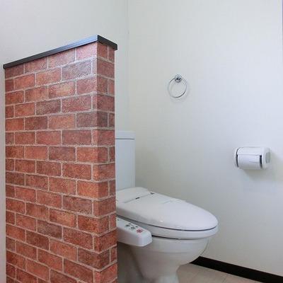 レンガ調の壁を半分はさんでトイレ空間があります