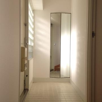 白タイルの玄関。姿見を開くとシューズボックスになっています。