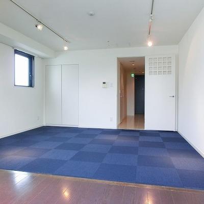 青いカーペットが敷かれたお部屋。ドアのデザインがいい感じ!