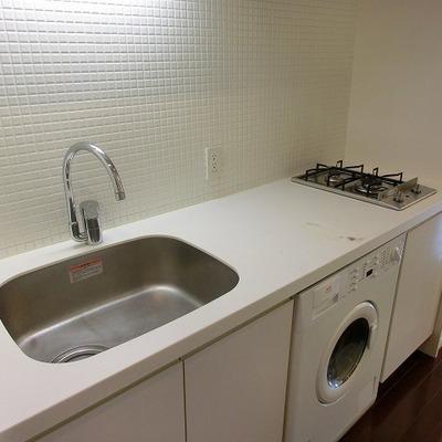 白タイルの2口コンロキッチンにはドラム式洗濯機付