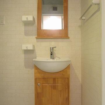 白いレンガ調のクロスに木製洗面台。かわいいね。