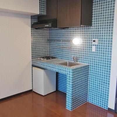 キッチン周りが青緑のタイル。※画像は別部屋