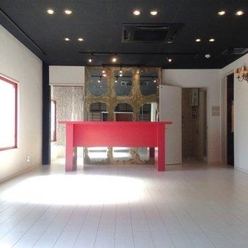 赤いテーブル、左奥にキッチン。おうちバー、始めます。
