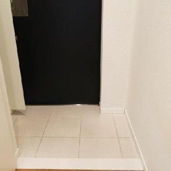 白いタイル張りの玄関※写真は別部屋