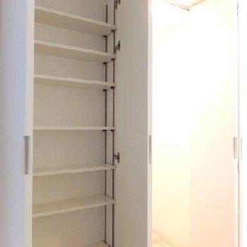 洗面台向かいに収納と洗濯機置場があります